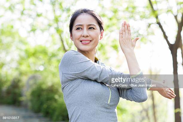 happy mature woman exercising in park - asian female bodybuilder stock photos and pictures