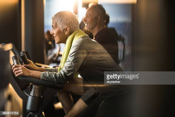 happy mature woman feeling determined on exercising class in a gym. - exercise bike stock photos and pictures