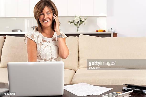 Heureuse femme mature remplir un document avec ordinateur portable