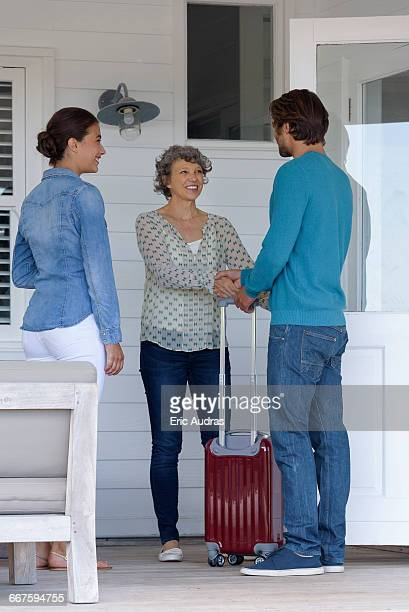 Happy mature woman greeting young couple at home