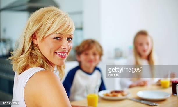 Happy mature woman having breakfast with her children