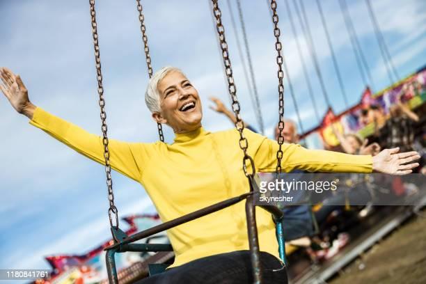 mulher madura feliz que tem o divertimento em um passeio chain do balanço no parque de diversões. - amarelo - fotografias e filmes do acervo
