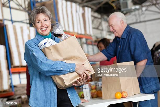 Heureuse femme mature tenant produits d'épicerie dans la cuisine coin cuisine