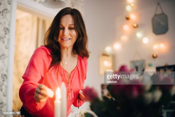 happy mature woman igniting candle in party at home - one mature woman only stock pictures, royalty-free photos & images