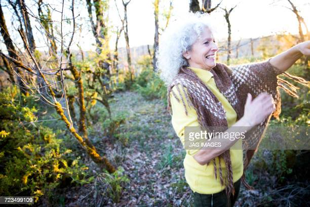 Happy mature woman in woodland scrub at sunset