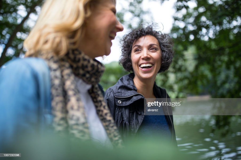 Happy mature woman looking at friend in forest : Stock Photo