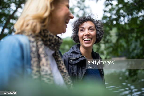 happy mature woman looking at friend in forest - só mulheres imagens e fotografias de stock