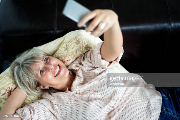 Happy mature woman lying down holding cell phone