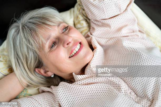 Happy mature woman lying down relaxing