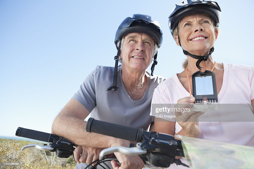 Happy mature woman mountain biking with man using GPS : Stockfoto