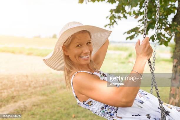 happy mature woman on swing in remote countryside - サンドレス ストックフォトと画像