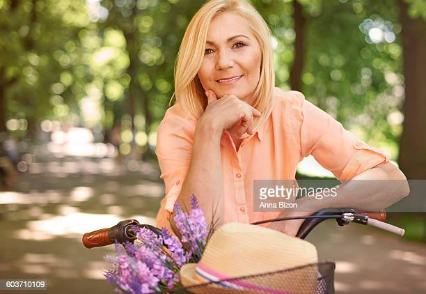 happy mature woman on the bike. krakow, poland - hand on chin stock pictures, royalty-free photos & images