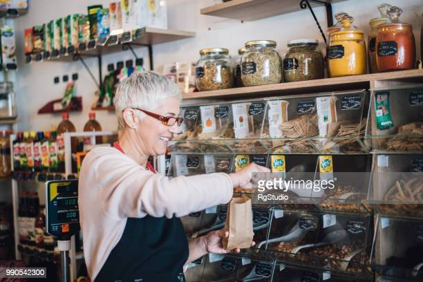 happy mature woman packing nuts in the paper bag - artisanal food and drink stock pictures, royalty-free photos & images