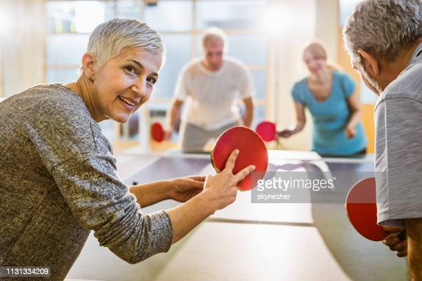 happy mature woman playing table tennis with her friends in health club. - table tennis stock pictures, royalty-free photos & images