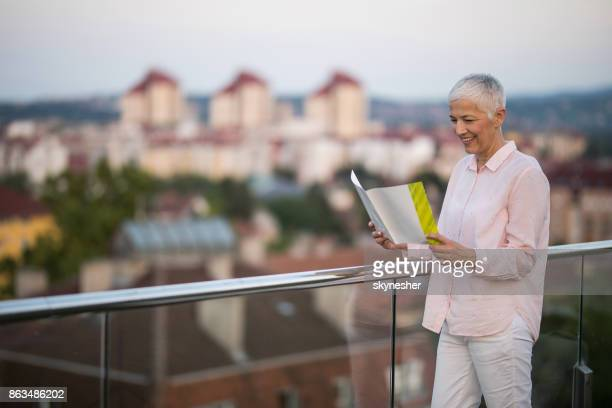 happy mature woman reading a magazine on a penthouse terrace. - penthouse magazine photos stock pictures, royalty-free photos & images