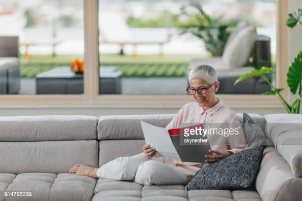 Glücklich Reife Frau Magazin und genießen an einem Tag zu Hause zu lesen.