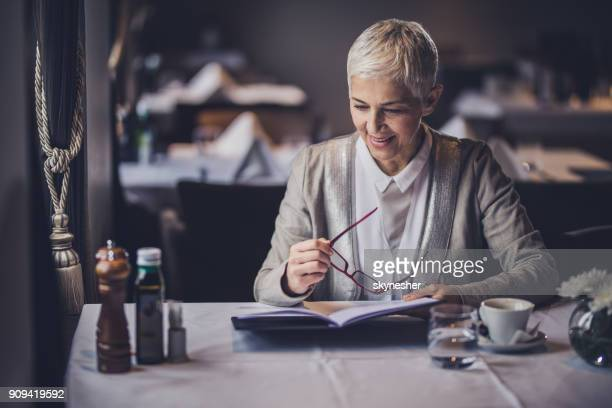happy mature woman reading menu in a restaurant. - menu stock pictures, royalty-free photos & images