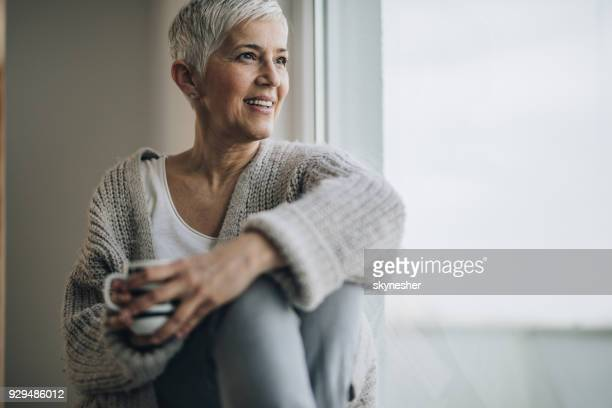 happy mature woman relaxing by the window during coffee time. - mature women stock pictures, royalty-free photos & images