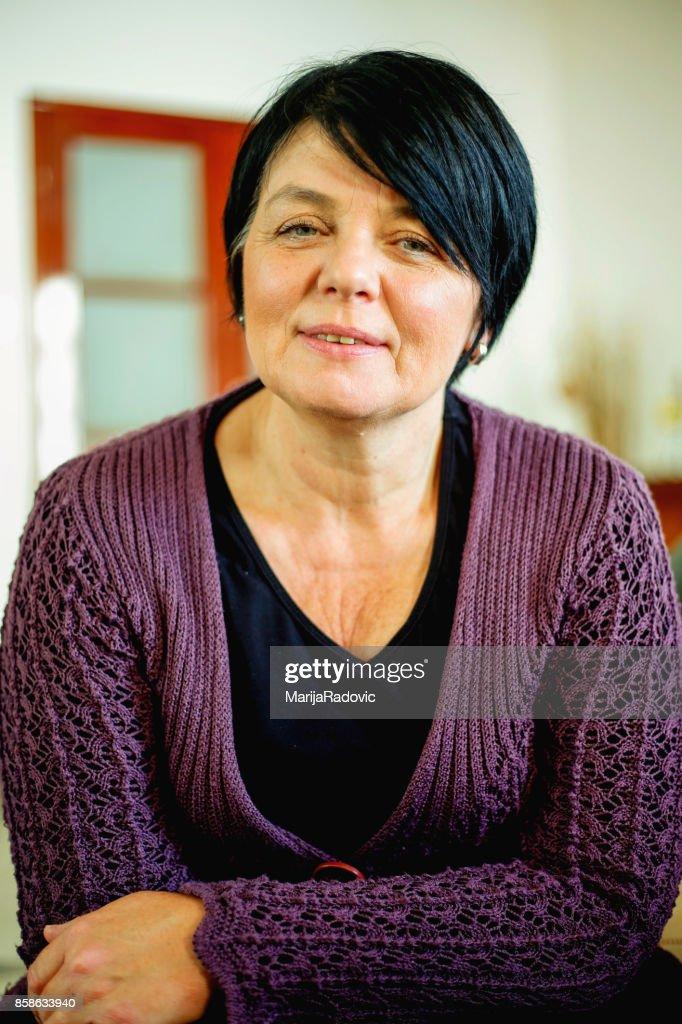 Glücklich Reife Frau entspannen Sie sich auf ihrer Couch zu Hause im Wohnzimmer : Stock-Foto