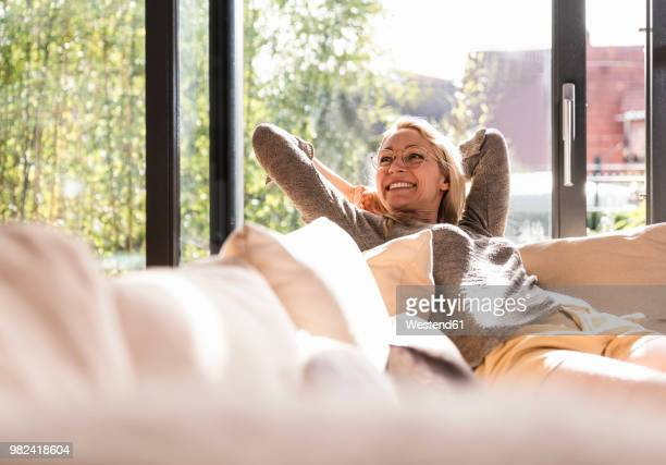 happy mature woman relaxing on the couch at home - zorgeloos stockfoto's en -beelden