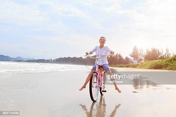 Happy mature woman riding bike on beach