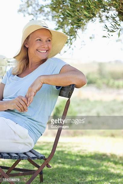 glückliche ältere frau sitzt im park - 55 59 jahre stock-fotos und bilder