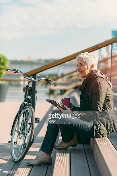 Happy Mature Woman Sitting On Stairs And Using digital Tablet.