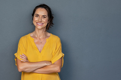 Happy mature woman smiling on grey wall 1180925302