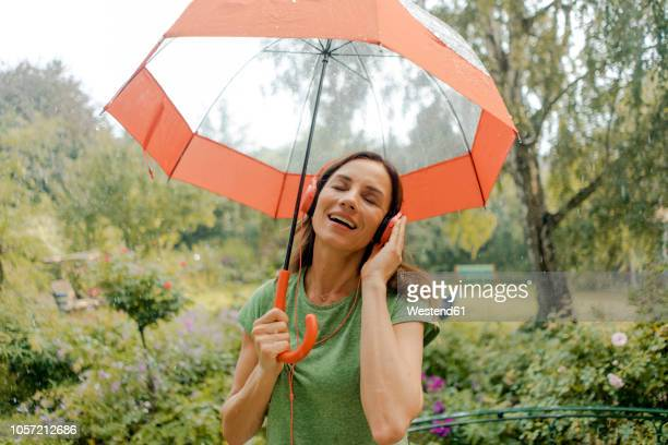 happy mature woman standing in rain under umbrella listening to music with headphones - women in wet t shirts stock pictures, royalty-free photos & images