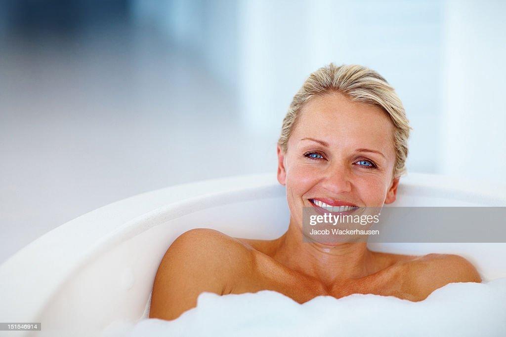 Happy mature woman taking bath : Stock Photo