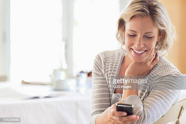 happy mature woman using cell phone at home - mature women stock pictures, royalty-free photos & images