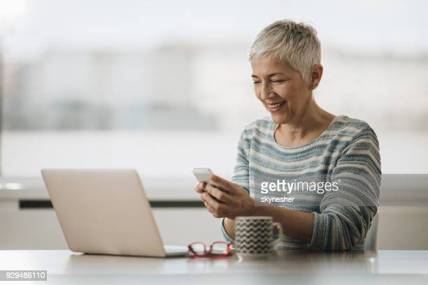 happy mature woman using cell phone while working on laptop at home. - candid forum stock pictures, royalty-free photos & images
