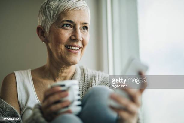happy mature woman using mobile phone by the window. - candid forum stock pictures, royalty-free photos & images