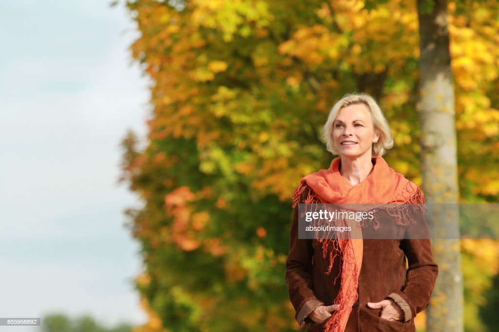 Happy mature woman walks in front of golden autumn leaves : Stock Photo