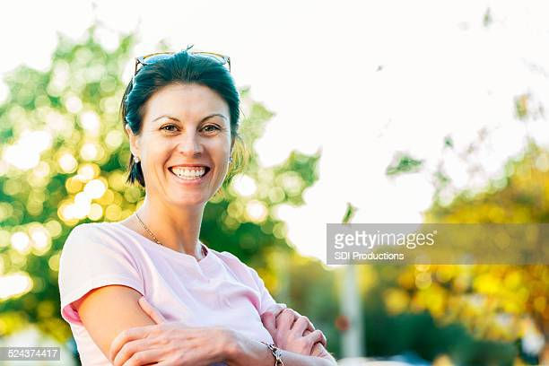 Happy mature woman wearing pink shirt for breast cancer awareness