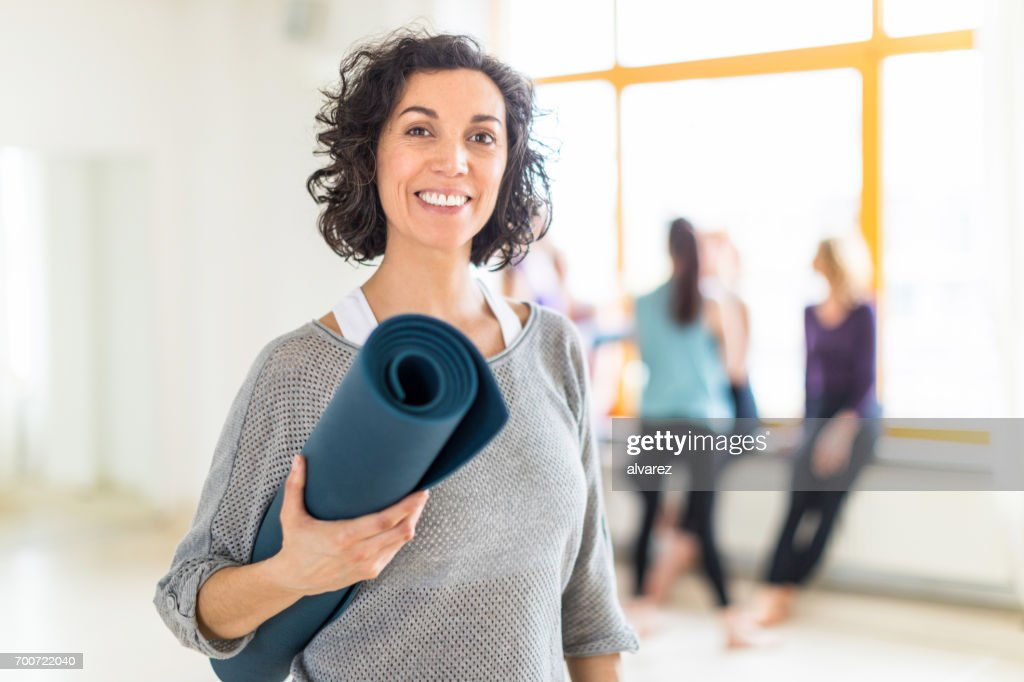 Happy mature woman with a yoga mat in health club : Stock Photo