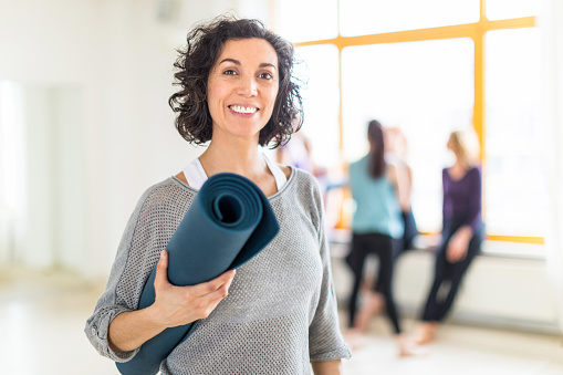 Happy mature woman with a yoga mat in health club - gettyimageskorea