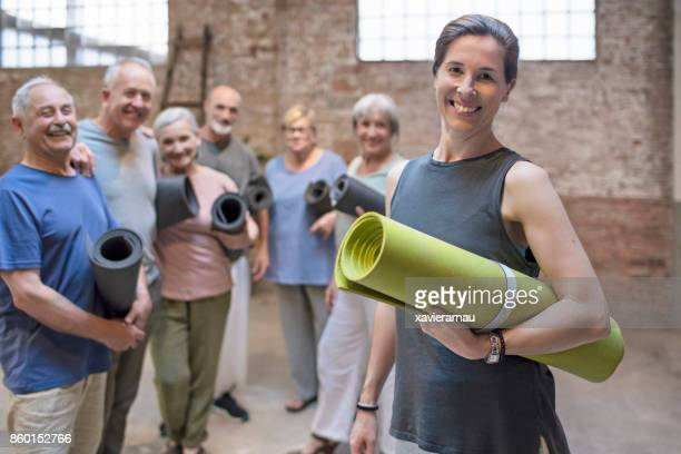 happy mature woman with a yoga mat in health club - yoga teacher stock pictures, royalty-free photos & images