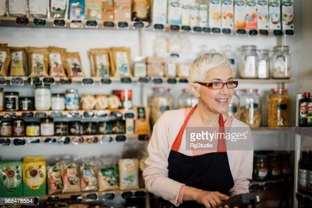 happy mature woman with calculator at healthy food store - part time job stock pictures, royalty-free photos & images