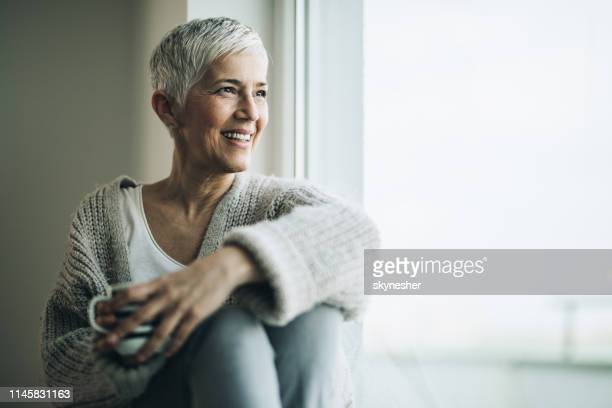 happy mature woman with coffee cup relaxing by the window. - mature women stock pictures, royalty-free photos & images
