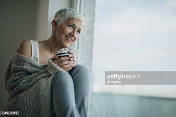 Happy mature woman with coffee cup relaxing by the window.