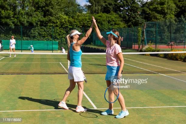happy mature women celebrating after tennis match - final game imagens e fotografias de stock