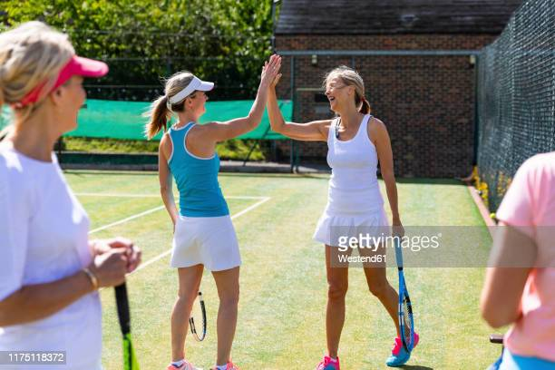 happy mature women celebrating after tennis match - tennis stock pictures, royalty-free photos & images
