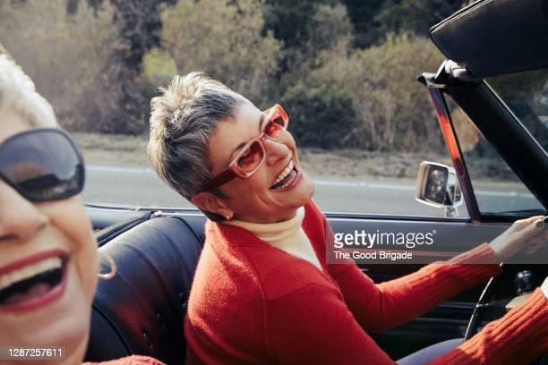 happy mature women driving in convertible car - disruptaging foto e immagini stock
