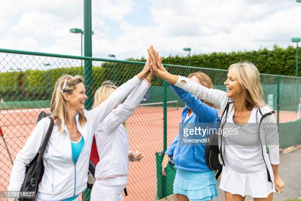 happy mature women high fiving at tennis club - tennis player stock pictures, royalty-free photos & images
