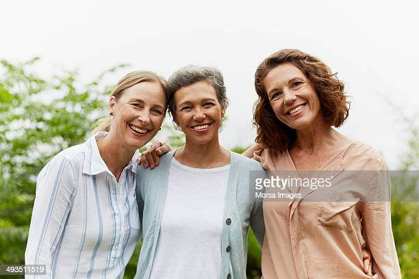 happy mature women standing in park - drei personen stock-fotos und bilder