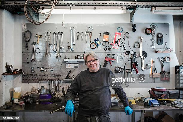 happy mechanic standing at tire shop - mechanic stock pictures, royalty-free photos & images