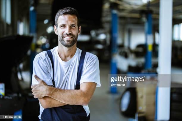 glücklicher mechaniker mit gekreuzten armen in autowerkstatt. - handwerker stock-fotos und bilder
