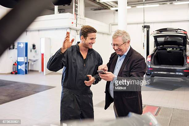 Happy mechanic with senior man using mobile app at auto repair shop