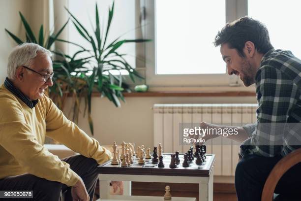 happy men playing chess - playing chess stock pictures, royalty-free photos & images